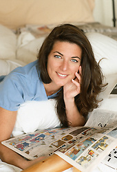 Woman in bed with The Funny Pages