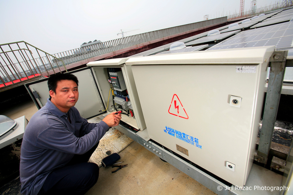 CHINA ZHEJIANG PROVINCE HANGZHOU 21MAY10 - Chinese engineer Pan Jiwu inspects the solar photovoltaic instlation on the rooftop of a building at the Energy and Environment Industial Park outside of the city of Hangzhou, China...jre/Photo by Jiri Rezac..© Jiri Rezac 2010