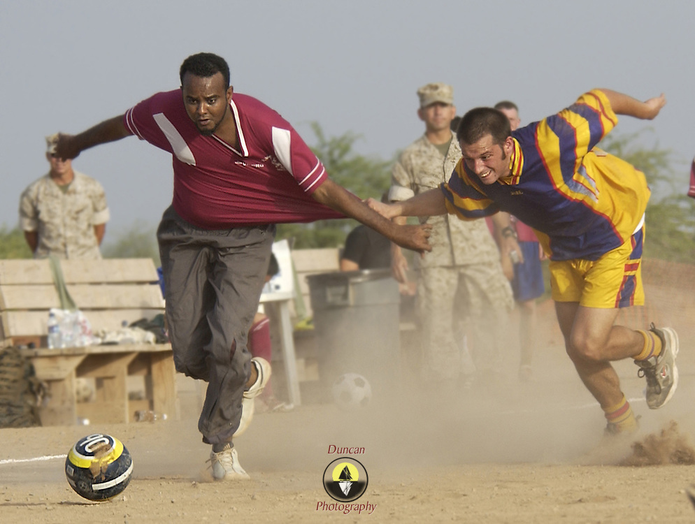 CAMP LEMONIER, Djibouti -- 05/29/06 -- Saleh, left, a Djiboutian employee of Camp Lemonier, sprints for the ball during an international soccer game held at Camp Lemonier. The German Navy, wearing yellow jerseys for the game, was resupplying at the Port of Djibouti and challenged Camp Lemonier to a 'futbol' match. The game's final score was not kept closely. U.S. Navy photo by Photographer's Mate 2nd Class Roger S. Duncan (RELEASED)