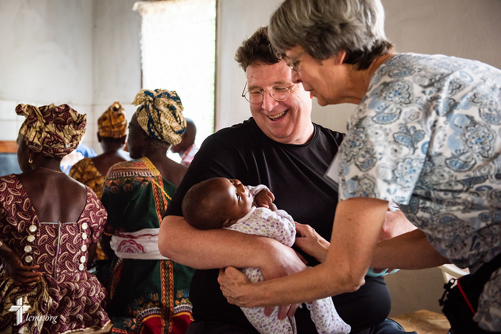 The Rev. Michael Awe, team leader and pastor at Hope Lutheran Church, South Sioux City, Neb., and Bonnie Hartman, a member of Faith Lutheran Church, Godfrey, Ill., spend a few joyful moments holding infant twins on the third day of the LCMS Mercy Medical Team on Wednesday, May 9, 2018, in the Yardu village outside Koidu, Sierra Leone, West Africa. LCMS Communications/Erik M. Lunsford