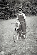 young adult male posing with bicycle and dog