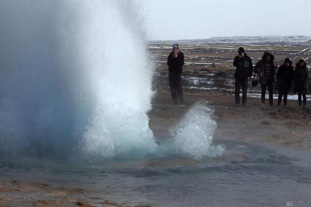 Tourists photograph the erupting Strokkur geyser at Geysir, South-West Iceland