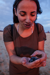 A beautiful girl receive a new born turtle, she will give her a name and let her go to the sea.