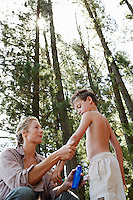 Mother Applying Suntan Lotion to Son (7-9) low angle view.