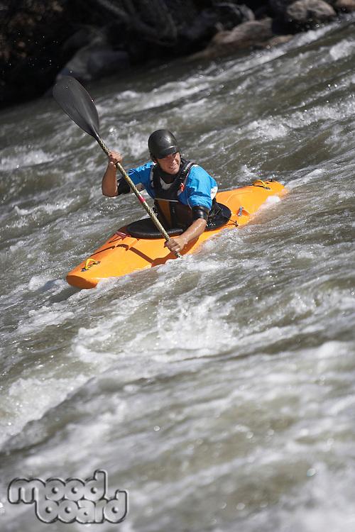 Man kayaking in mountain river
