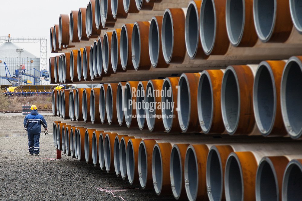 A port worker walking through piles of gas pipe destined for the abandoned South Stream gas pipeline, in the port of Burgas, Bulgaria. Photo by Rob Arnold