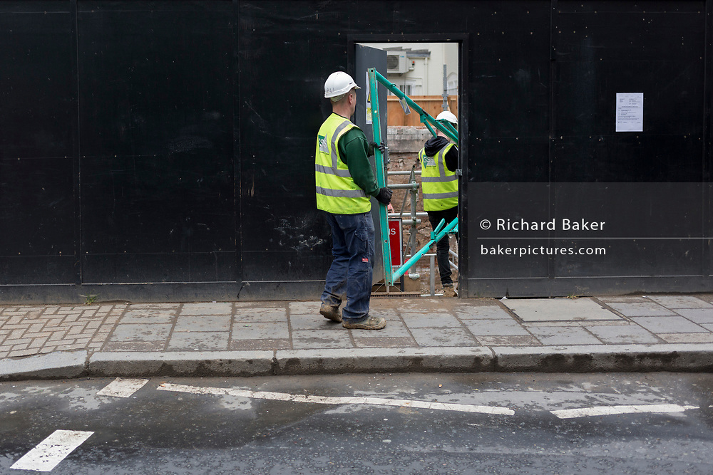 Two workmen carry a frame through the doorway of a nearby construction site, on 8th April 2019, in London, England