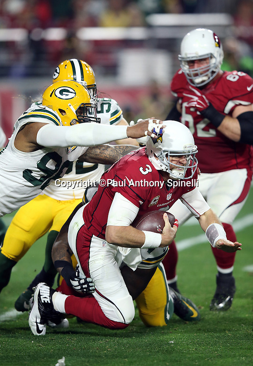 Arizona Cardinals quarterback Carson Palmer (3) gets sacked in the second quarter by Green Bay Packers defensive end Mike Daniels (76) and Green Bay Packers outside linebacker Mike Neal (96) during the NFL NFC Divisional round playoff football game against the Green Bay Packers on Saturday, Jan. 16, 2016 in Glendale, Ariz. The Cardinals won the game in overtime 26-20. (©Paul Anthony Spinelli)