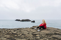 Young woman in red sitting on cliffs at Dyrholaey