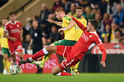 Swindon Town's Harry Smith (right) slides in to tackle Norwich City's Harrison Reed during the Carabao Cup, first round match at Carrow Road, Norwich.