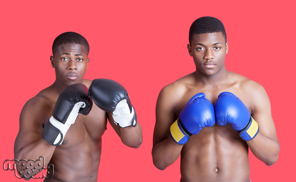 Portrait of two African American boxers wearing gloves over red background