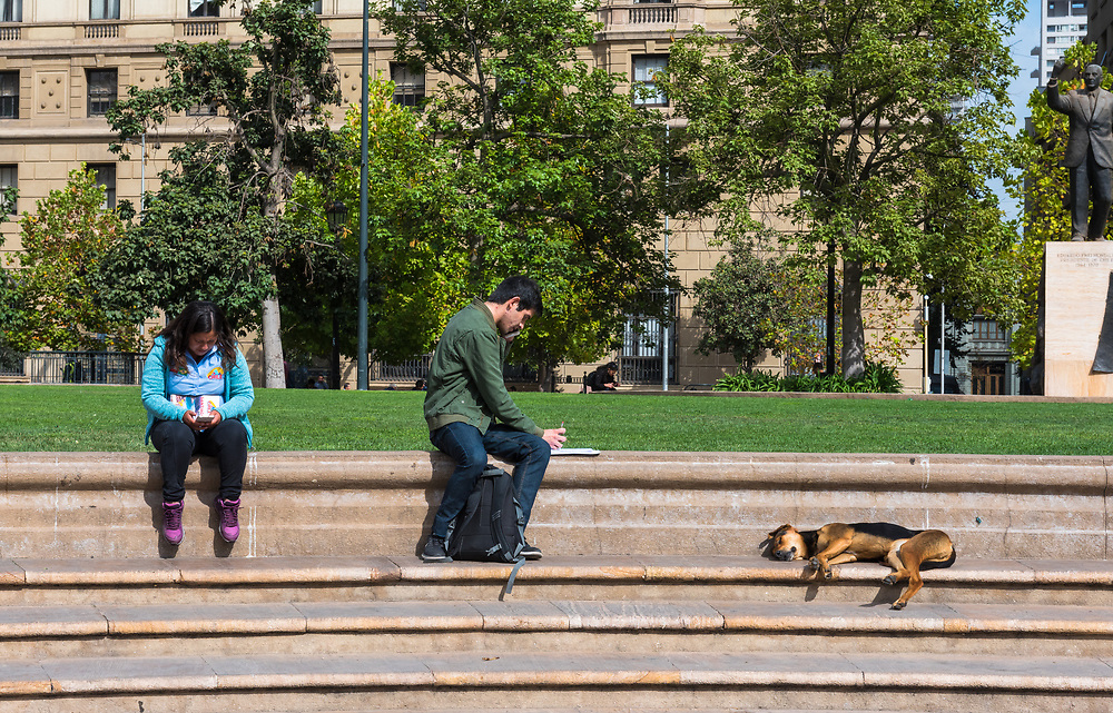 Santiago, Chile--April 6, 2018. Two people are sitting on steps by a park while a dog sleeps nearby. Editorial use only.