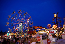 Festival with people and ferris wheel at dusk