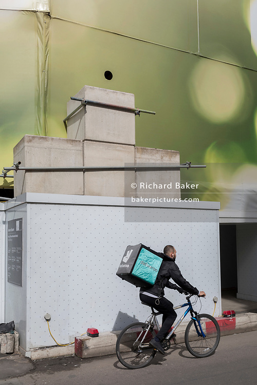 A Deliveroo rider cycles past large concrete blocks, part of a construction site on the corner of Brook and New Bond Streets, on 6th April 2018, in London, England.