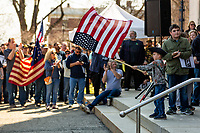 A young boy, wearing a patriot cap, waves a large American flag on the steps of the Hartford State Capitol building yesterday during the 2nd Amendment rally.
