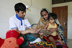 """September 18, 2016 - Dhaka, Bangladesh - Tahera, 3, daughter of Abul Bajandar , touches her father's hand at a hospital bad in Dhaka, Bangladesh, September 18, 2016. Doctors carried out several operations to remove extremely rare epidermodysplasia verruciformis warts from his hands and legs.  Abul, who was admitted to DMCH on January 30, has been suffering from an extremely rare genetic skin disease epidermodysplasia verruciformis, which is also referred to as """"Tree Man Disease."""" The disease is caused by a defect in the immune system. It causes abnormal susceptibility to human papilloma viruses (HPVs), which eventually leads to the overgrowth of scaly macules and papules, especially on the feet and hands. Abul is the fifth person in the world reported to be suffering from the disease. (Credit Image: © Suvra Kanti Das via ZUMA Wire)"""