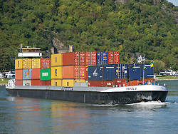 Barge carrying containers sailing up the River Rhine in Germany