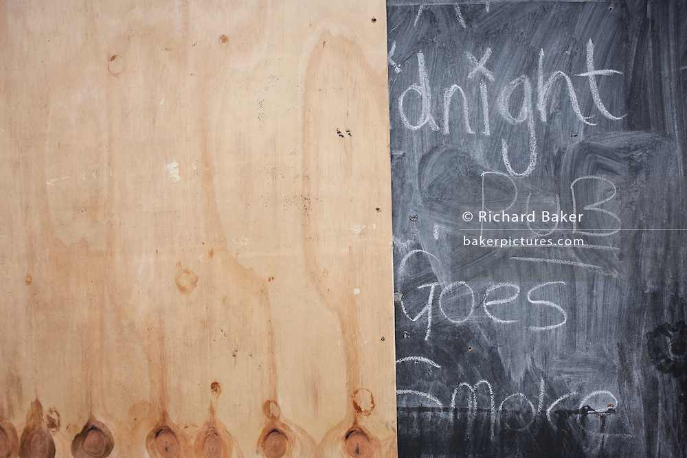 MDF board obscuring a blackboard advertising enterntainment in a closed pub on wasteland in  Canning Town, Newham..