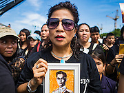 22 OCTOBER 2016 - BANGKOK, THAILAND:  A woman holds a portrait of the late Bhumibol Adulyadej, the King of Thailand, during the singing of the King's Anthem on Sanam Luang Saturday. Sanam Luang, the Royal Ceremonial Ground, was packed Saturday with more than 100,000 people mourning the Monarch's death. The King died Oct. 13, 2016. He was 88. His death came after a period of failing health. Bhumibol Adulyadej was born in Cambridge, MA, on 5 December 1927. He was the ninth monarch of Thailand from the Chakri Dynasty and is also known as Rama IX. He became King on June 9, 1946 and served as King of Thailand for 70 years, 126 days. He was, at the time of his death, the world's longest-serving head of state and the longest-reigning monarch in Thai history.      PHOTO BY JACK KURTZ