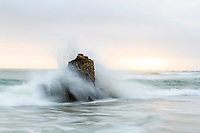 Waves breaking over a rocky outcrop at sunset, Buffalo Bay, Western Cape, South Africa