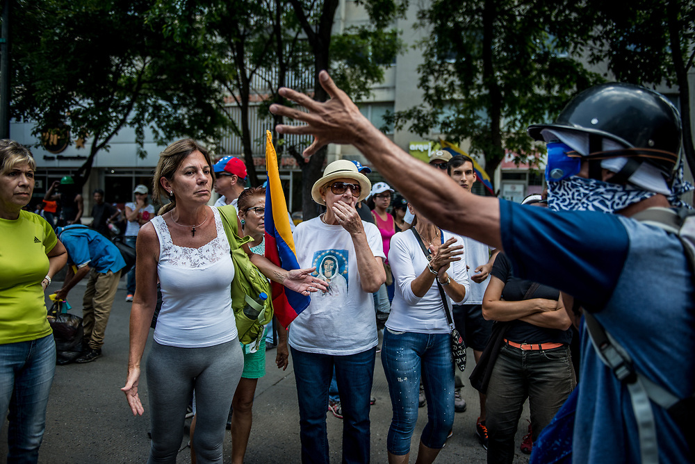 "CARACAS, VENEZUELA - May 27, 2017: A member of ""The Resistance"", a hardline group of anti-government protesters, argues with nonviolent protesters that were attending an opposition rally that included live musicians and beer stands, just blocks from where members of ""The Resistance"" were being tear gassed and shot at with rubber bullets and buckshot by security forces. The member of ""The Resistance"" was angry and frustrated, shouting: ""We are over there fighting and getting killed, and you are here dancing?!"" The streets of Caracas and other cities across Venezuela have been filled with tens of thousands of demonstrators for nearly 100 days of massive protests, held since April 1st. Protesters are enraged at the government for becoming an increasingly repressive, authoritarian regime that has delayed elections, used armed government loyalist to threaten dissidents, called for the Constitution to be re-written to favor them, jailed and tortured protesters and members of the political opposition, and whose corruption and failed economic policy has caused the current economic crisis that has led to widespread food and medicine shortages across the country.  Independent local media report nearly 100 people have been killed during protests and protest-related riots and looting.  The government currently only officially reports 75 deaths.  Over 2,000 people have been injured, and over 3,000 protesters have been detained by authorities.  PHOTO: Meridith Kohut"