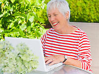 A mature woman working outside on her patio with a laptop computer