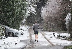 © Licensed to London News Pictures. 27/12/2017. Dorking, UK. Despite the snow showers and low temperatures a runner jogs near the village of Coldharbour in the Surrey Hills. Photo credit: Peter Macdiarmid/LNP