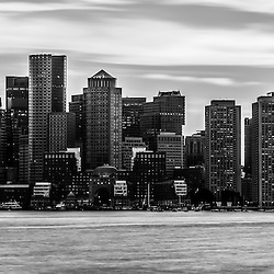 Boston skyline black and white panoramic picture. Scene includes Boston downtown city skyscraper buildings across Boston Harbor.