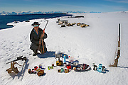 Emil Madsen, a seal hunter, with his typical day's worth of food on the sea ice in front of his sleeping sled dogs near Cap Hope village, Greenland. (From the book What I Eat: Around the World in 80 Diets.) MODEL RELEASED.