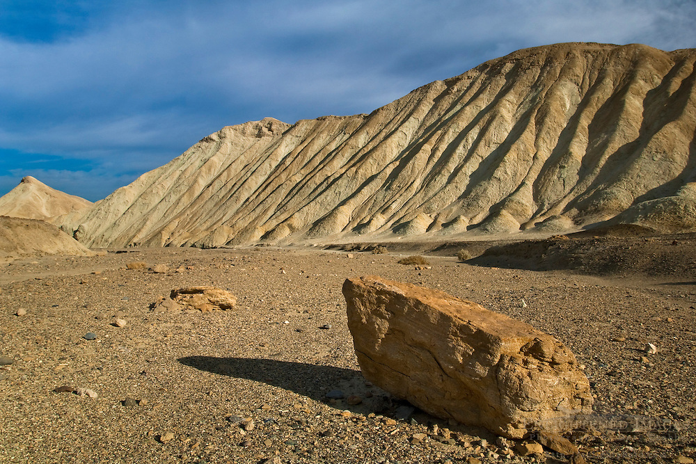 Lone rock below eroded hillside, Twenty Mule Team Canyon, Death Valley National Park, California