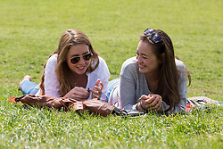 © Licensed to London News Pictures. 14/05/2014. London, UK. Two women chat as they enjoy the sunshine and good weather in Regents Park in London on 14th May 2014.. Photo credit : Vickie Flores/LNP
