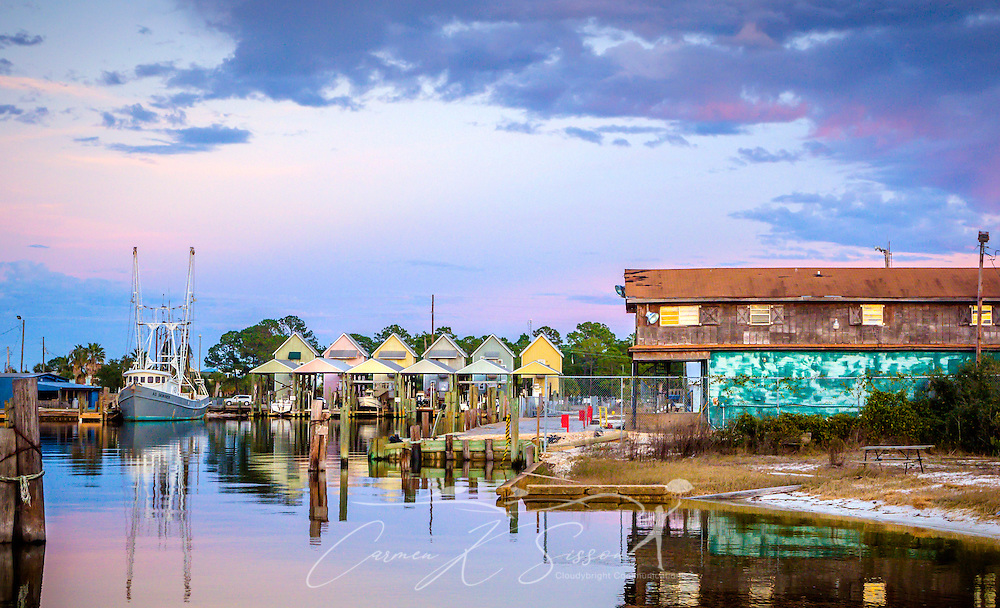 A patio seat at JT's Sunset Grill, located downstairs below the Pelican Pub on DeSoto Avenue, offers a tranquil view of the sunset over Bayou Aloe, Jan. 17, 2015, in Dauphin Island, Alabama. (Photo by Carmen K. Sisson/Cloudybright)