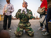 """31 JANUARY 2013 - PHNOM PENH, CAMBODIA:   A Cambodian Army officer prays for former King Norodom Sihanouk in front of the Royal Palace in Phnom Penh. Sihanouk (31 October 1922- 15 October 2012) was the King of Cambodia from 1941 to 1955 and again from 1993 to 2004. He was the effective ruler of Cambodia from 1953 to 1970. After his second abdication in 2004, he was given the honorific of """"The King-Father of Cambodia."""" Sihanouk served two terms as king, two as sovereign prince, one as president, two as prime minister, as well as numerous positions as leader of various governments-in-exile. He served as puppet head of state for the Khmer Rouge government in 1975-1976. Most of these positions were only honorific, including the last position as constitutional king of Cambodia. Sihanouk's actual period of effective rule over Cambodia was from 9 November 1953, when Cambodia gained its independence from France, until 18 March 1970, when General Lon Nol and the National Assembly deposed him. Upon his final abdication, the Cambodian throne council appointed Norodom Sihamoni, one of Sihanouk's sons, as the new king. Sihanouk died in Beijing, China, where he was receiving medical care, on Oct. 15, 2012. His funeral procession, which will wind through Phnom Penh is Friday, Feb.1 and his cremation is on Feb. 4, 2013. Over a million people are expected to attend the service.   PHOTO BY JACK KURTZ"""