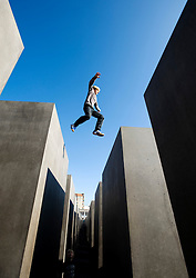 Boy jumping between concrete pillars at the Holocaust Memorial in central Berlin Germany