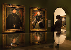 "© Licensed to London News Pictures. 09/10/2013. London, England. A visitor stands in front of the paintings ""Thomas Howard, 4th Duke of Norfolk"" by Hans Eworth and ""Margaret Dudley, Duchess of Norfolk"" by Hans Eworth, 1562. Press preview of the exhibition ""Elizabeth I & Her People"" at the National Portrait Gallery which explores the remarkable reign of Elizabeth I through the lives and portraiture of her subjects. Exhibition runs from 10 October 2013 to 5 January 2014. Photo credit: Bettina Strenske/LNP"