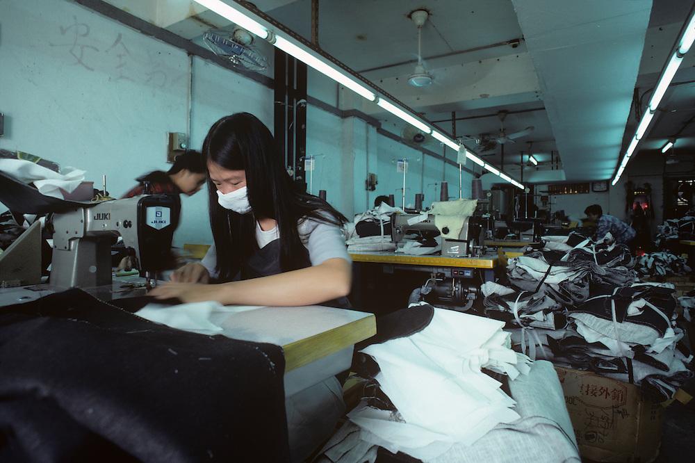 China, Hong Kong, Woman works in garment sweatshop in New Territories