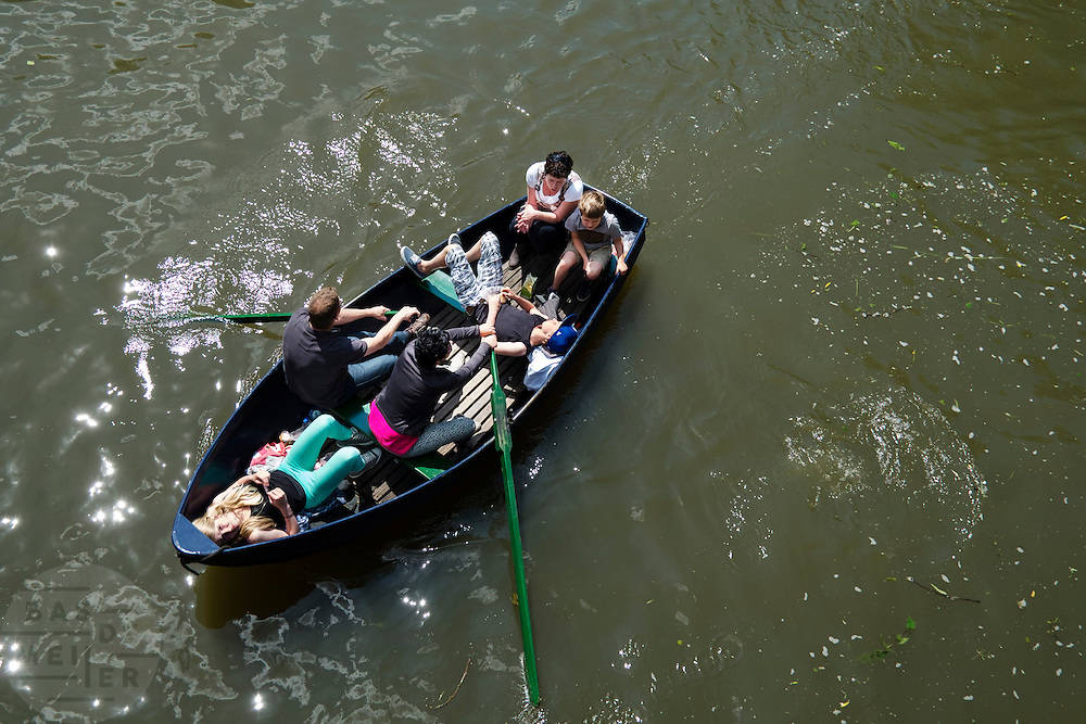 Een gezin vaart in een roeiboot door de grachten van Utrecht. <br />