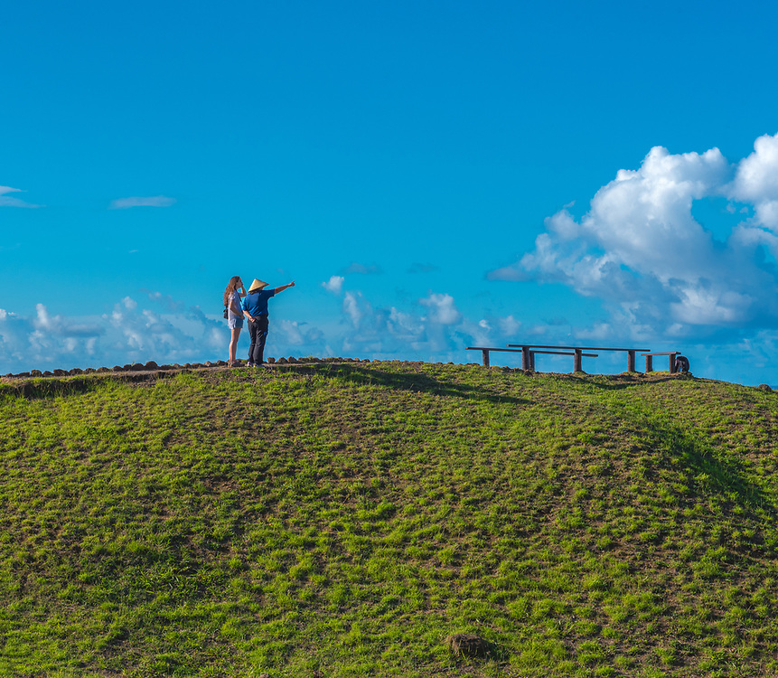 Easter Island, Chile -- March 30, 2018. Woman pointing toward the distance from a hill on Easter Island, Chile. Editorial Use Only.