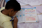 A young Egyptian boy practices his English words from a textbook at his home in the village of Bairat, on the West Bank of Luxor, Nile Valley, Egypt.