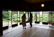 Visitors admire the Kakubuen garden from the first floor reception room of the main building of the Honma Museum of Art in Sakata, Yamagata Prefecture, Japan, on July 06, 2012. Construction of the garden and reception room was started around 200 years ago. Photographer: Robert Gilhooly