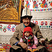 Kyrgyz man and baby, blending western and traditional life, near Murgab, Tajikistan