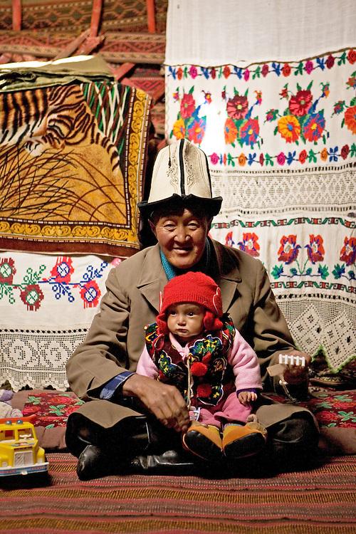 Kyrgyz man and baby, blending western and traditional life, near Murgab, Tajikistan