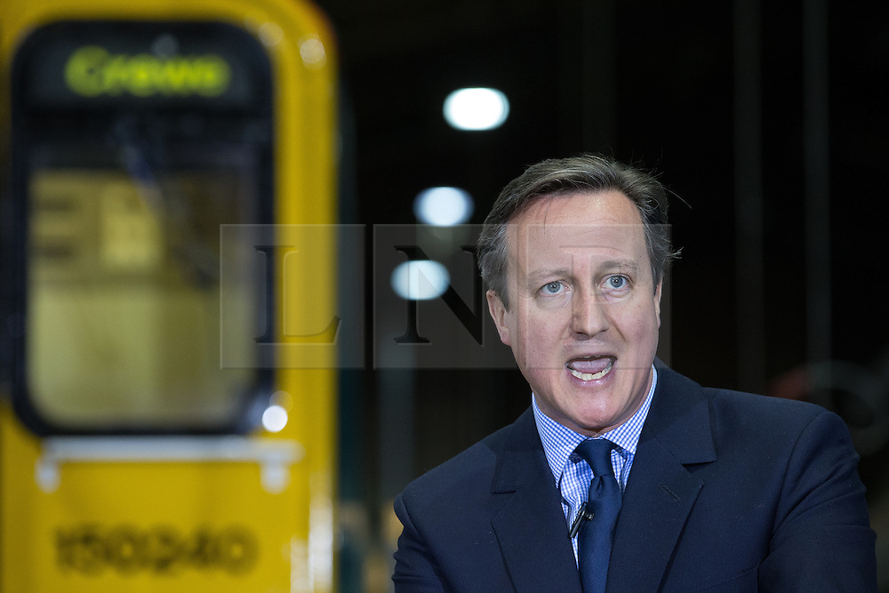 © Licensed to London News Pictures . 20/04/2015 . Crewe , UK . DAVID CAMERON and George Osborne campaigning in an Arriva train shed in Crewe , Cheshire as part of the Conservative Party's election run . Photo credit : Joel Goodman/LNP