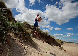© Paul Thompson licensed to London News Pictures. 03/06/2015. Nicholas Tidswell-Thompson (4) jumps off sand dunes at Warkworth Beach Northumberland. Photo credit : Paul Thompson/LNP