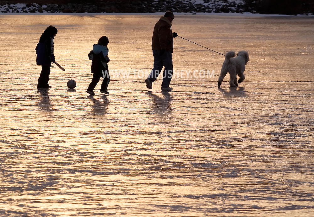 Monroe, N.Y. - A girl, a boy, a man and a dog walk across the ice on the Mill Pond  on Feb. 11, 2007.