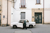 """PISCIOTTA, ITALY - 22 APRIL 2018: An elderly man enters his car in the historical center of Pisciotta, Italy, on April 22nd 2018.<br /> <br /> Former restaurant owners Donatella Marino and her husband Vittorio Rimbaldo have spent the recent years preparing and selling salted anchovies, called alici di menaica, to a growing market thanks to a boost in visibility from the non-profit Slow Food.  The ancient Menaica technique is named after the nets they use brought by the Greeks wherever they settled in the Mediterranean. Their process epitomizes the concept of slow food, and involves a nightly excursion with the special, loose nets that are built to catch only the larger swimmers. The fresh, red anchovies are immediately cleaned and brined seaside, then placed in terracotta pots in between layers of salt, to rest for three months before they're aged to perfection.While modern law requires them to use PVC containers for preserving, the government recently granted them permission to use up to 10 chestnut wood barrels for salting in the traditional manner. The barrels are """"washed"""" in the sea for 2-3 days before they're packed with anchovies and sea salt and set aside to cure for 90 days. The alici are then sold in round terracotta containers, evoking the traditional vessels that families once used to preserve their personal supply.<br /> <br /> Unlike conventional nets with holes of about one centimeter, the menaica, with holes of about one and half centimeters, lets smaller anchovies easily swim through. The point may be to concentrate on bigger specimens, but the net also prevents overfishing."""