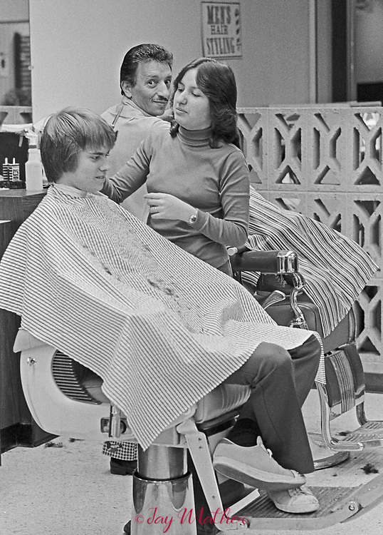 Verna Archuleta works in a barber shop in Westminster, CO in 1977. Once a man's world, barbershops changed as more women entered the workforce. Ms. Archuleta received her degree from the Colorado Barber College in Denver, 1976. Eventually she went on to get a B.A. in Business Management from Colorado State University and now works as an online marketing consultant in Golden, CO. My career in barbering started because my Dad was a Barber. The barbershop was  in Thornton on 84th and I25, in the North Valley Mall. The shop was named Archies barbershop. It was my dad's shop and his nickname was Archie. The Barber standing behind me was my Dad. <br /> We lived in Westminster,  I  was going to Westminster High School. I was probably 16 in this photo. I was the youngest student to take the barbering state boards in Colorado.  I believe your interest began with my VICA class in school. The teacher Mr. Malucca (I believe that was his name) bragged about me being in a predominantly male field and so young.