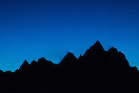 The grand tetons silhoutted against the deep blue sky of twilight