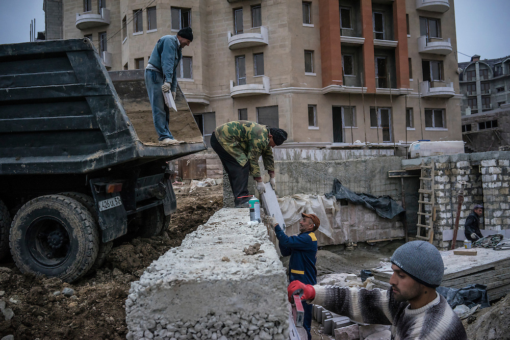 STEPANAKERT, NAGORNO-KARABAKH - APRIL 20: Construction workers build a cluster of brand new apartment buildings on April 20, 2015 in Stepanakert, Nagorno-Karabakh. Since signing a ceasefire in a war with Azerbaijan in 1994, Nagorno-Karabakh, officially part of Azerbaijan, has functioned as a self-declared independent republic and de facto part of Armenia, with hostilities along the line of contact between Nagorno-Karabakh and Azerbaijan occasionally flaring up and causing casualties. (Photo by Brendan Hoffman/Getty Images) *** Local Caption ***