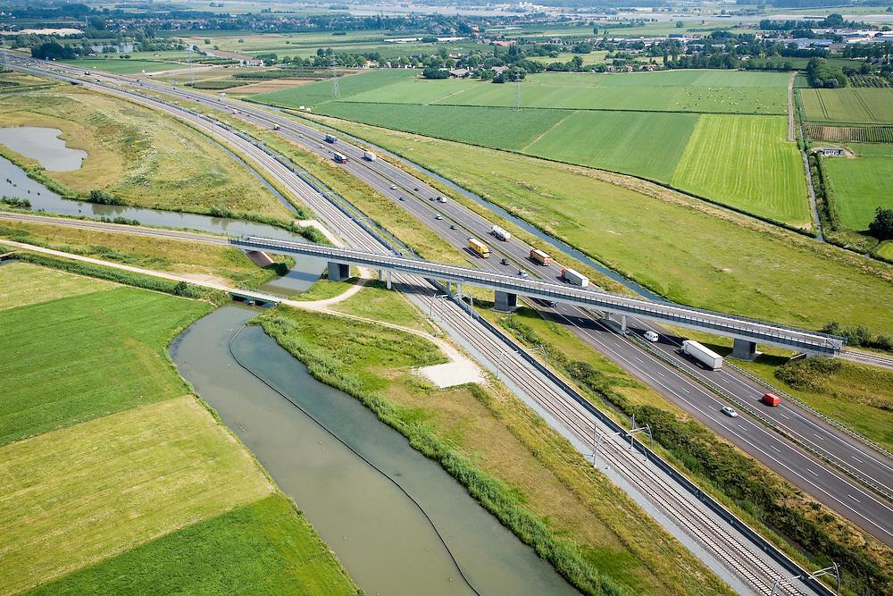 Nederland, Gelderland, Echteld, 28-06-2006; de spoorlijn Tiel-Elst, met nieuw viaduct over de verlegde autosnelweg A15, deze buigt af naar Ochten (Oostelijk), in de voorgrond het water van de rivier de Linge en de nieuw aangelegde Betuweroute; deze kruising van verschillende infrastuctur is aangelegd in het kader van de bouw van de Betuweroute; de landweg naast de spoorlijn heet saneringsweg, naam afkomstig uit de tijd van de ruilverkaveling, sanering fruitteelt;Betuwelijn, lokale verbindingsweg, verkeer en vervoerbouw, transport, infrastructuur, infrabundel, mobiliteit, planologie; zie ook luchtfoto's van de bouwfase en andere foto's van deze lokatie; deel van de serie Panorama Nederland luchtfoto (toeslag aerial photo (additional fee required .foto Siebe Swart / photo Siebe Swart